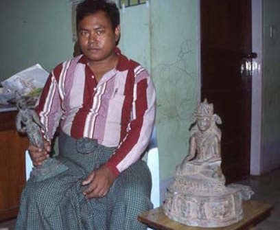 """The """"Mandalay Master"""" responsible for a wave of fake Buddhist bronzes that even entered museum collections. An Indian Chola bronze in one hand, with a fake Burmese bronze looking on. He is rumoured to have gone missing somewhere along the Burma-Thai border."""
