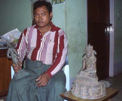"The ""Mandalay Master"" responsible for a wave of fake Buddhist bronzes that even entered museum collections. An Indian Chola bronze in one hand, with a fake Burmese bronze looking on. He is rumoured to have gone missing somewhere along the Burma-Thai border."